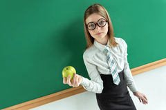 Free Attractive Pupil In Round Glasses Holding Green Apple. Royalty Free Stock Photos - 75643188