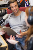 Attractive radio host interviewing a guest holding clipboard Stock Photo
