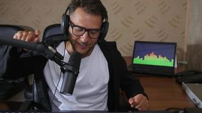 Attractive radio presenter with glasses and earphones leads radio broadcast at studio. Attractive radio presenter with glasses and earphones leads radio stock footage