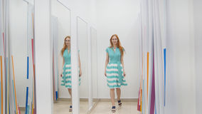 Attractive red hair girl chooses green dress near mirror in fitting room at store stock photos