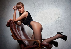 Attractive red hair model with black corset sitting provocatively on chair Stock Photography