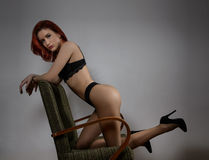Attractive red hair model with black lingerie sitting provocatively on chair, gray background. Fashion portrait of sensual woman Stock Images