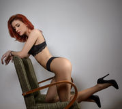 Attractive red hair model with black lingerie sitting provocatively on chair, gray background. Fashion portrait of sensual woman. Studio shot. Beautiful Royalty Free Stock Photography
