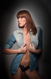 Attractive red hair model with black panties and denim shirt standing on gray background. Fashion portrait of a sensual woman Stock Photography
