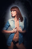 Attractive red hair model with black panties and denim shirt standing on gray background. Fashion portrait of a sensual woman Stock Image