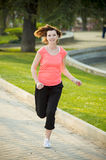 Attractive red hair woman running in the park Royalty Free Stock Photo