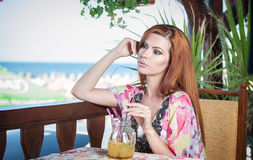 Attractive red hair young woman with bright colored blouse drinking lemonade on a terrace having blue sea in background Royalty Free Stock Photo