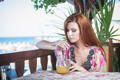 Attractive red hair young woman with bright colored blouse drinking lemonade on a terrace having blue sea in background Royalty Free Stock Image