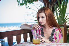 Attractive red hair young woman with bright colored blouse drinking lemonade on a terrace having blue sea in background Stock Photography