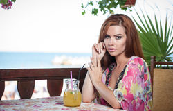 Attractive red hair young woman with bright colored blouse drinking lemonade on a terrace having blue sea in background Stock Photos