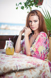 Attractive red hair young woman with bright colored blouse drinking lemonade on a terrace having blue sea in background Stock Images