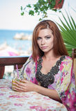 Attractive red hair young woman with bright colored blouse drinking lemonade on a terrace having blue sea in background Stock Image