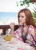 Attractive red hair young woman with bright colored blouse drinking lemonade on a terrace having blue sea in background Royalty Free Stock Photos