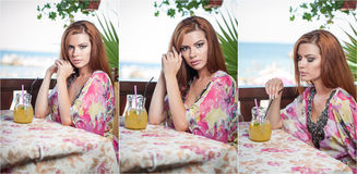 Attractive red hair young woman with bright colored blouse drinking lemonade on a terrace having blue sea in background Royalty Free Stock Images