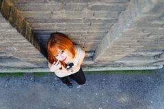 Attractive red haired cute young girl standing beside the wall Stock Images
