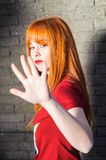 Attractive red haired freckled young girl doing stop sign with her hand Stock Photo