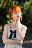 Attractive red haired freckled young girl touching her neck at outdoor Stock Images
