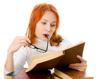 Attractive red-haired girl in glasses reads book. Royalty Free Stock Image