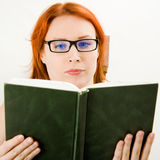 Attractive red-haired girl in glasses reads book. Royalty Free Stock Photos