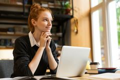 Attractive red haired teenage girl using laptop computer stock photos