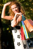 Attractive red-haired woman with shopping bags Stock Photos