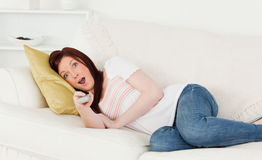 Attractive red-haired woman watching tv Royalty Free Stock Images