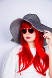 Attractive red-haired young woman in sunglasses and hat on white Royalty Free Stock Images