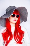 Attractive red-haired young woman in sunglasses and hat on white Stock Photo