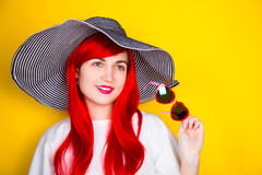 Attractive red-haired young woman in sunglasses and hat on yello Stock Image