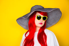 Attractive red-haired young woman in sunglasses and hat on yello Royalty Free Stock Photography