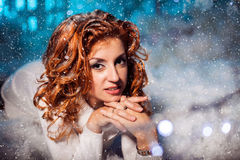 Attractive red head girl kneeling on all four among snowdrift Royalty Free Stock Photos
