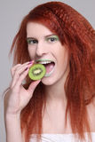 Attractive redhaired girl with biting kiwi Royalty Free Stock Photos