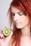 Attractive redhaired girl with kiwi over white Stock Image