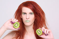 Attractive redhaired woman with kiwi Stock Images