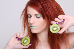 Attractive redhaired woman with kiwi Royalty Free Stock Image