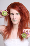 Attractive redhaired woman with kiwi Royalty Free Stock Photos