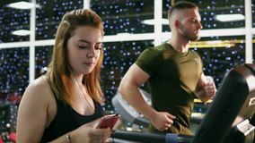 Attractive redhead caucasian girl is walking on the treadmill in the sport gym with earphones. Shot in 4K.  stock footage