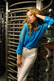 Attractive redhead fashion model posing pretty by entrance with revolving door Stock Image