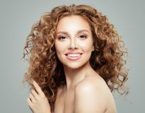 Attractive redhead girl with clear skin and long healthy curly hair. Beautiful female face on gray background.  royalty free stock images