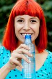 Redhead girl drinking water in a park Royalty Free Stock Photos