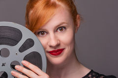 Attractive redhead holding film reel Royalty Free Stock Images