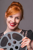 Attractive redhead holding film reel Stock Photos