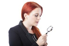 Attractive redhead holding a magnifying glass Royalty Free Stock Photos