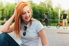 Attractive redhead smiling girl in casual clothes sitting on street in city, active people on background stock images