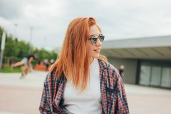 Attractive redhead smiling girl in round sunglasses in casual clothes sitting on street in city royalty free stock photos