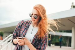 Attractive redhead smiling girl in round sunglasses with phone in her hands in casual clothes listening music on street in city royalty free stock images
