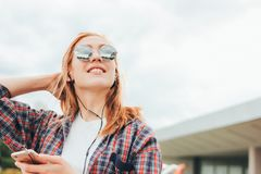 Attractive redhead smiling girl in round sunglasses with phone in her hands in casual clothes listening music on street in city royalty free stock image