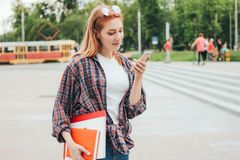 Attractive redhead smiling girl student with phone in her hands in casual clothes on street in city stock photography