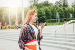Attractive redhead smiling girl student with phone in her hands in casual clothes on street in city stock image