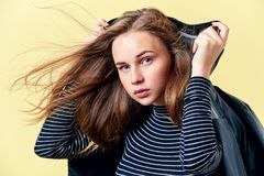 Attractive redhead teenager with freckles posing for fashion portrait in a black leather jacket. On pastel yellow coloured background Royalty Free Stock Images